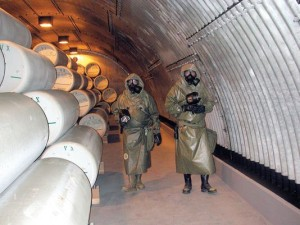 "WORKERS IN POISON-PROOF SUITS EXAMINE VX NERVE GAS CYLINDERS AT A FEDERAL DISPOSAL SITE IN NORTHEAST INDIANA. THESE DAYS, NERVE GAS AND OTHER MILITARY POISONS CAN BE SAFELY NEUTRALIZED ON LAND. DURING THE COLD WAR, THOUGH, LEFTOVER MUNITIONS WERE DUMPED IN THE ATLANTIC, PACIFIC, AND GULF OF MEXICO, ON THE THEORY OF ""OUT OF SIGHT, OUT OF MIND."" TO THIS DAY, THEY REST ON OCEAN FLOORS, THEIR STEEL FANGS DRIPPING POISON, READY TO SPEW DEATH IF DISTURBED. WORKERS IN POISON-PROOF SUITS EXAMINE VX NERVE GAS CYLINDERS AT A FEDERAL DISPOSAL SITE IN NORTHEAST INDIANA. THESE DAYS, NERVE GAS AND OTHER MILITARY POISONS CAN BE SAFELY NEUTRALIZED ON LAND. DURING THE COLD WAR, THOUGH, LEFTOVER MUNITIONS WERE DUMPED IN THE ATLANTIC, PACIFIC, AND GULF OF MEXICO, ON THE THEORY OF ""OUT OF SIGHT, OUT OF MIND."" TO THIS DAY, THEY REST ON OCEAN FLOORS, THEIR STEEL FANGS DRIPPING POISON, READY TO SPEW DEATH IF DISTURBED."